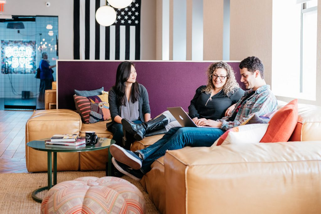 three people working in the lounge of a coworking space